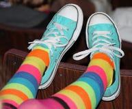 Skraj randiga sockor och trendiga turkosgymnastikskor arkivfoton