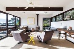 Skraj retro vardagsrum för strandhus med 70-talstilstolar arkivbild