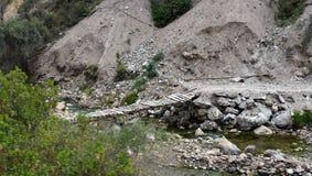 Skrangligt gå bron över stenig liten vik Arkivfoto