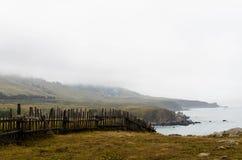 Skrangligt staket i bygden på en dimmig dag royaltyfria bilder