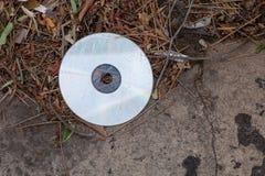 Skrapad och smutsig CD i avloppsrännan Royaltyfri Bild