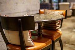 Skrapade det inre stället för konst med stolar, tabeller och kuddar inomhus i stads- tappningkafé med grå färger väggar Fotografering för Bildbyråer