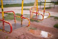 Skrapade gungor på lekplatsen fotografering för bildbyråer