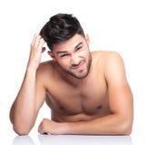 Skrapar den nakna mannen för förvirrad skönhet hans huvud Arkivbild