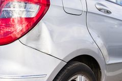 Skrapor och bucklor på silverbilen efter olycka royaltyfri bild