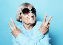 Skratt för gammal kvinna och uppvisning av fred- eller segersignatkameran Sinnesrörelse och känslor Stående av den uttrycksfulla  royaltyfri foto
