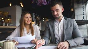 Skratta affärskvinnan med legitimationshandlingar som talar till hennes kollega under möte i kafé arkivfilmer