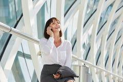 Skratta affärskvinnan som talar på den smarta telefonen i terminal Royaltyfri Foto