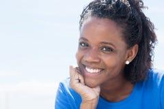 Skratta afrikansk amerikankvinnan i en blå skjorta royaltyfri foto