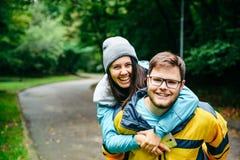 Skratta bär par i sport, kvinnan hoppar på manskuldror arkivbild