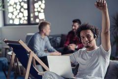 Skratta bärare för afrikansk amerikanhipsterprogramvara på datoren på kontoret av det startup företaget arkivbild