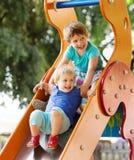Skratta barn på glidbana Fotografering för Bildbyråer