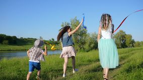 Skratta barn som kör och vinkar med kulöra band på naturen nära floden lager videofilmer