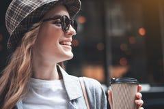 Skratta damen i moderiktiga skuggor med koppen kaffe royaltyfria foton