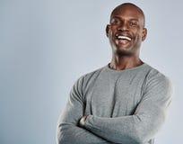 Skratta den afrikanska mannen i grå skjorta med kopieringsutrymme royaltyfria foton
