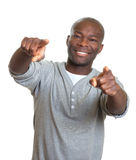 Skratta den afrikanska mannen som pekar med två fingrar på kameran arkivbilder