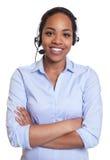 Skratta den afrikanska telefonoperatören med hörlurar med mikrofon som ser kameran Arkivfoton