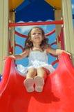 Skratta den förskole- flickan på lekplatsen royaltyfria bilder
