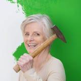 Skratta den höga kvinnan som gör att dekorera för inre Arkivfoton