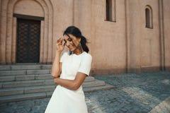 Skratta den indiska damen i den vita klänningen mot forntida byggnad Royaltyfri Bild
