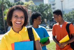 Skratta den kvinnliga studenten för afrikansk amerikan med gruppen av annan stu Royaltyfri Fotografi