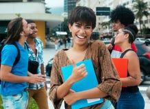 Skratta den latinska flickan med gruppen av mång- etniska studenter i stad Arkivbild