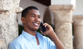 Skratta den latinska grabben med telefonen i en kolonial stad Arkivfoton