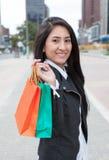 Skratta den latinska kvinnan med två shoppingpåsar Arkivbilder