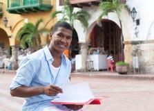 Skratta den latinska studenten i en kolonial stad med skrivbordsarbete Fotografering för Bildbyråer