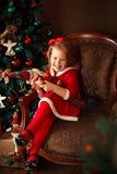 Skratta den lilla flickan med dekorativ jultomten Arkivbild