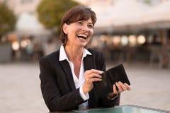 Skratta den livliga kvinnan som gör en betalning Arkivbilder