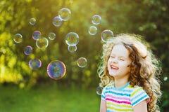 Skratta den lockiga flickan med bubblor Arkivbild