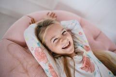 Skratta den lyckliga flickan som ligger på en rosa kudde royaltyfria bilder