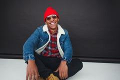 Skratta den moderiktiga etniska mannen i studio fotografering för bildbyråer
