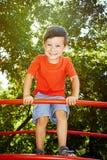 Skratta den nätta pojken i röd t-skjorta Royaltyfri Foto