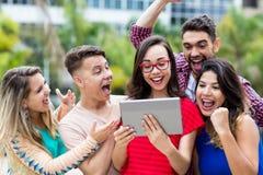 Skratta den nerdy franska kvinnliga studenten med minnestavladatoren och gruppen av att hurra internationella studenter royaltyfria foton