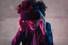 Skratta den tonåriga flickan som bär VR-hörlurar med mikrofon royaltyfri foto