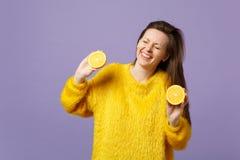 Skratta den unga kvinnan i pälströjan som håller ögon stängda, hållhalfs av ny mogen orange frukt som isoleras på violett pastell arkivfoton