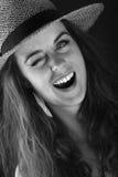 Skratta den unga kvinnan med hatten Arkivbild