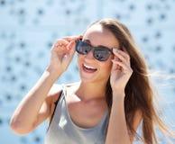 Skratta den unga kvinnan med solglasögon Fotografering för Bildbyråer