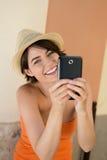 Skratta den unga kvinnan som fotograferar sig Royaltyfri Bild
