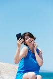 Skratta den unga kvinnan som fotograferar sig Arkivfoton