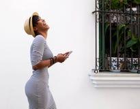 Skratta den unga kvinnan som går med mobiltelefonen Fotografering för Bildbyråer