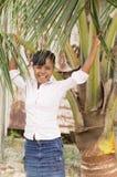 Skratta den unga kvinnan som stoppas under en kokospalm arkivfoto