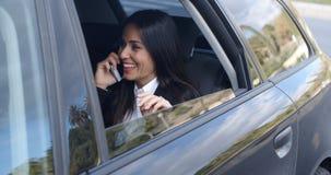 Skratta den unga ledaren på telefonen i bil Royaltyfria Foton