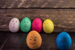 Skratta easter ägg på lantliga träplankor lyckliga easter Arkivbild