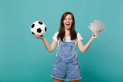 Skratta för fotbollsfanservice för ung kvinna det favorit- laget med fotbollbollen, fan av pengar i dollarsedlar, kassapengar royaltyfri bild