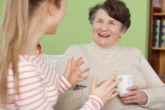 Skratta för sondotter och för mormor arkivbild