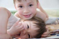 Skratta för ungar, lyckliga barn som ler ståenden som tillsammans spelar syskon, lilla flickan och pojken, syskongrupp Arkivfoto