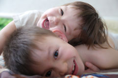 Skratta för ungar, lyckliga barn som ler ståenden som tillsammans spelar syskon, lilla flickan och pojken, syskongrupp Royaltyfria Bilder